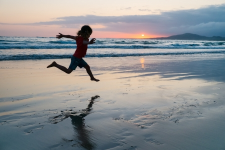 one little girl: Silhouette of adorable little girl on a beach at sunset
