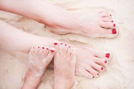 beach feet: Close up of mother and daughter feet on a tropical sandy beach