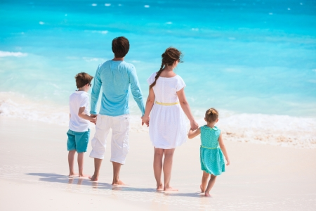 Back view of a Caucasian family at tropical beach photo