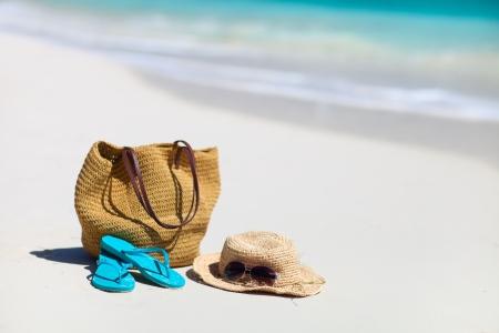flip flops: Straw hat, bag, sun glasses and flip flops on a tropical beach