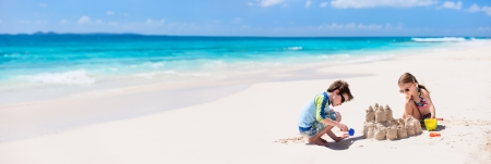 sand castle: Brother and sister making sand castle at tropical beach Stock Photo