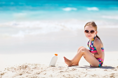 sun lotion: Little girl with bottle of sun cream sitting at tropical beach Stock Photo