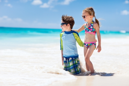 Brother and sister enjoying time at tropical beach photo
