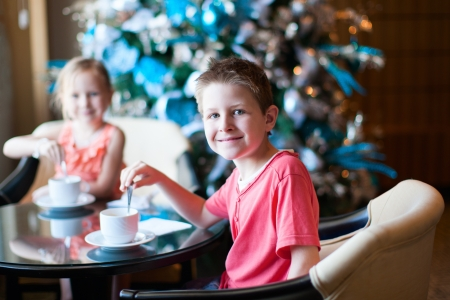 cofffee: Two children drink tea from white cups Stock Photo