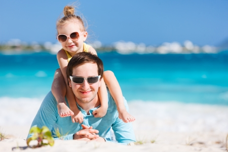 Happy father and his adorable little daughter at beach photo