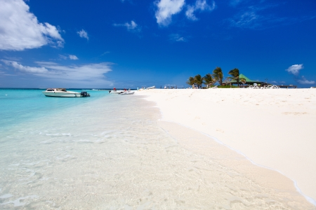 anguilla: Crystal clear water and white sand beach, boat on the water Stock Photo