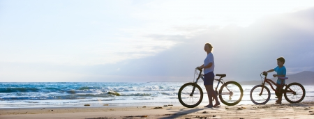 ecotourism: Panorama of mother and son biking on a beach at sunset Stock Photo