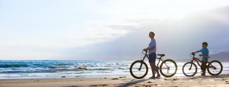 Panorama van moeder en zoon fietsen op een strand bij zonsondergang
