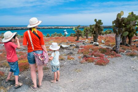 ecotourism: Mother and two kids hiking at scenic terrain on Galapagos South Plaza island