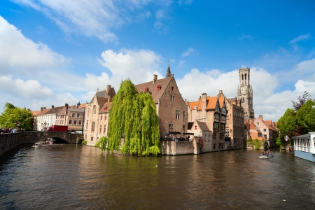 bruges: Canal in Bruges with the famous Belfry tower on the background
