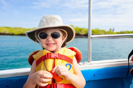 Adorable little girl in a life jacket travelling on boat photo