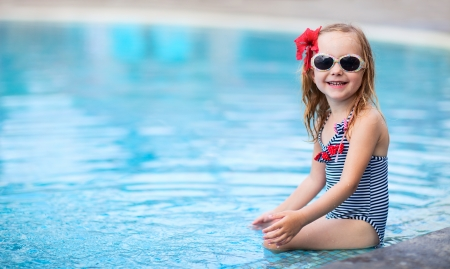 Portrait of adorable little girl near a swimming pool