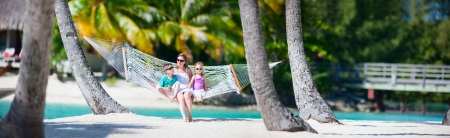 bora bora: Mother and two kids relaxing on hammock at tropical beach