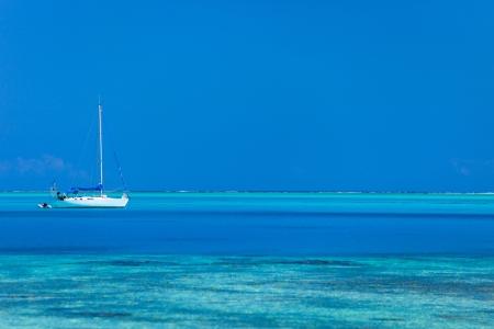 White yacht at stunning tropical lagoon of Bora Bora photo