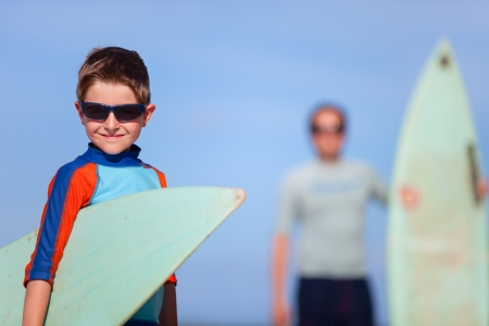 Portrait of father and son with surfboards photo