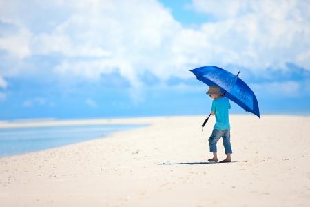 Little boy with umbrella walking along tropical beach photo