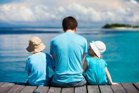 fun: Back view of father and kids sitting on wooden dock looking to ocean