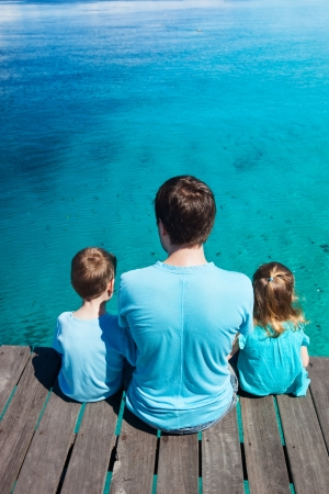 wooden dock: Back view of father and kids sitting on wooden dock looking to ocean