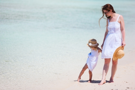 Beautiful mother and little daughter at tropical beach Stock Photo