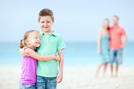 Kids embracing each other while parents standing on background photo