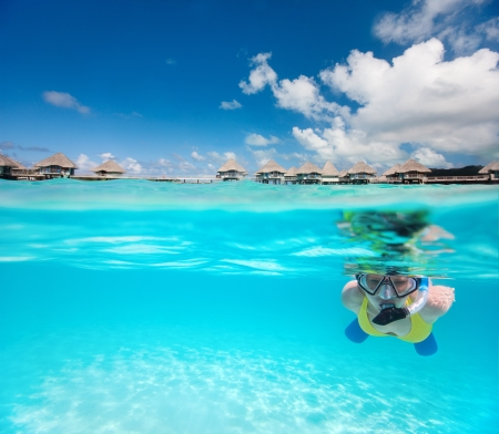 Woman snorkeling in clear tropical waters in front of overwater villas photo