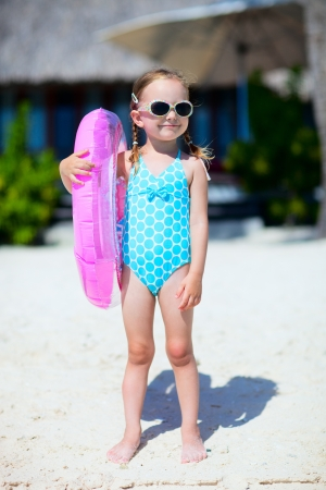 Portrait of cute little girl in swim suit at tropical beach photo