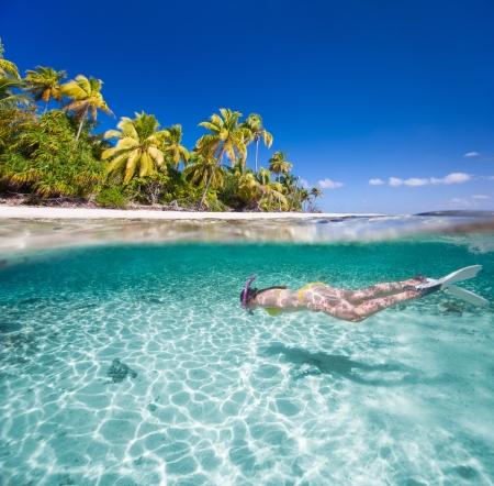 Vrouw zwemmen onderwater in duidelijke tropische wateren in de voorkant van exotische eiland Stockfoto