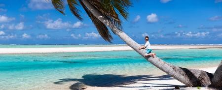 tahiti: Little boy sitting on a palm at exotic beach