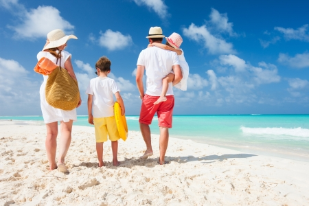 Back view of a happy family on tropical beach Stock Photo