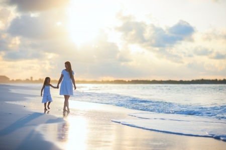 Mother and her little daughter walking along a beach on sunset photo