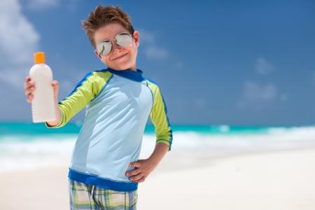 Cute little boy at tropical beach holding a bottle of sunblock photo