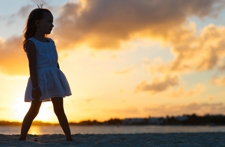 Silhouette of adorable little girl on a beach at sunset photo