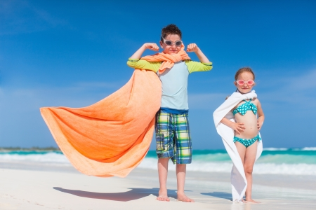 Little kids playing superheroes at a tropical beach