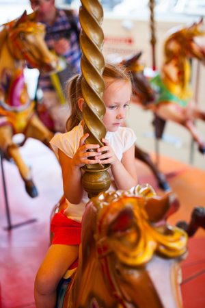 amusement park ride: Adorable little girl having fun on a Merry-Go-Round carousel