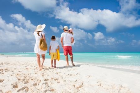 Achteraanzicht van een gelukkige familie op tropische strand Stockfoto