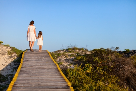 Back view of mother and daughter walking along a wooden path