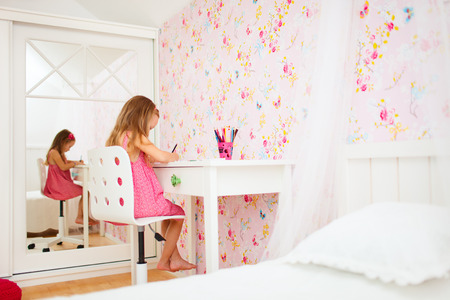Adorable little girl in her room drawing