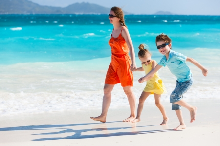 Mother and kids on a Caribbean vacation walking along a beach photo