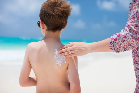 Close up of a mother applying sunblock cream on her son photo