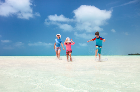 Mother and kids on a Caribbean vacation running at shallow water photo