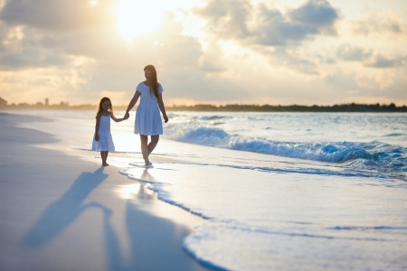 mother with daughter: La madre y su pequeña hija caminando por una playa en la puesta del sol