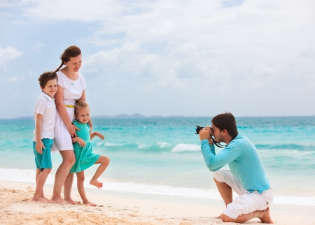 photographing: Young man making photo of his wife and kids at tropical beach Stock Photo