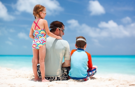 Back view of father and kids enjoying beach vacation photo