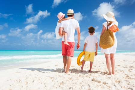 Back view of a happy family on tropical beach Archivio Fotografico