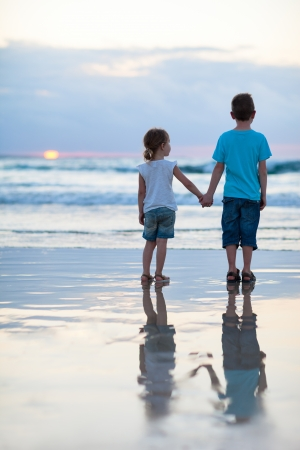 Brother and sister on beach at sunset