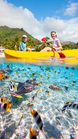 Mother and son kayaking in a tropical lagoon photo