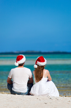 Romantic couple in Santa hats sitting on a tropical beach photo