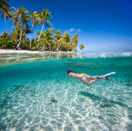 underwater woman: Woman swimming underwater in clear tropical waters in front of exotic island Stock Photo