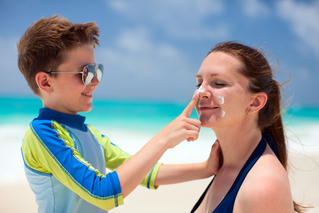 Little boy applying sun cream to her mother nose photo