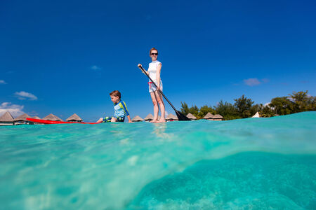 paddleboard: Mother and son paddle boarding together